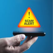 person holding a phone with scam alert icon
