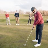 4 men golfing, 1 in the forefront of image