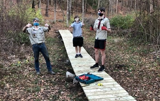 three boy scouts posing with wood board walk they built