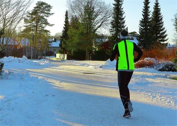man jogging on snowy road