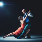 two people doing the tango against black background