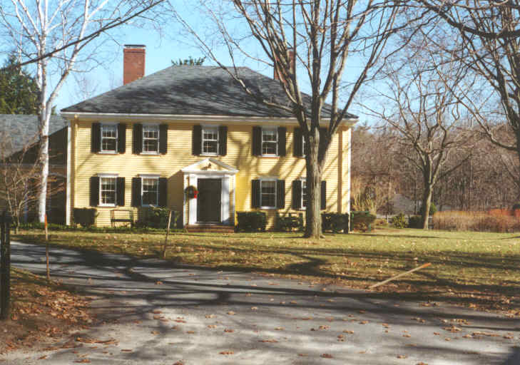 A Colonial style home with yellow siding