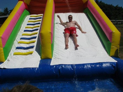 A man sliding down a pool inflatable.jpg